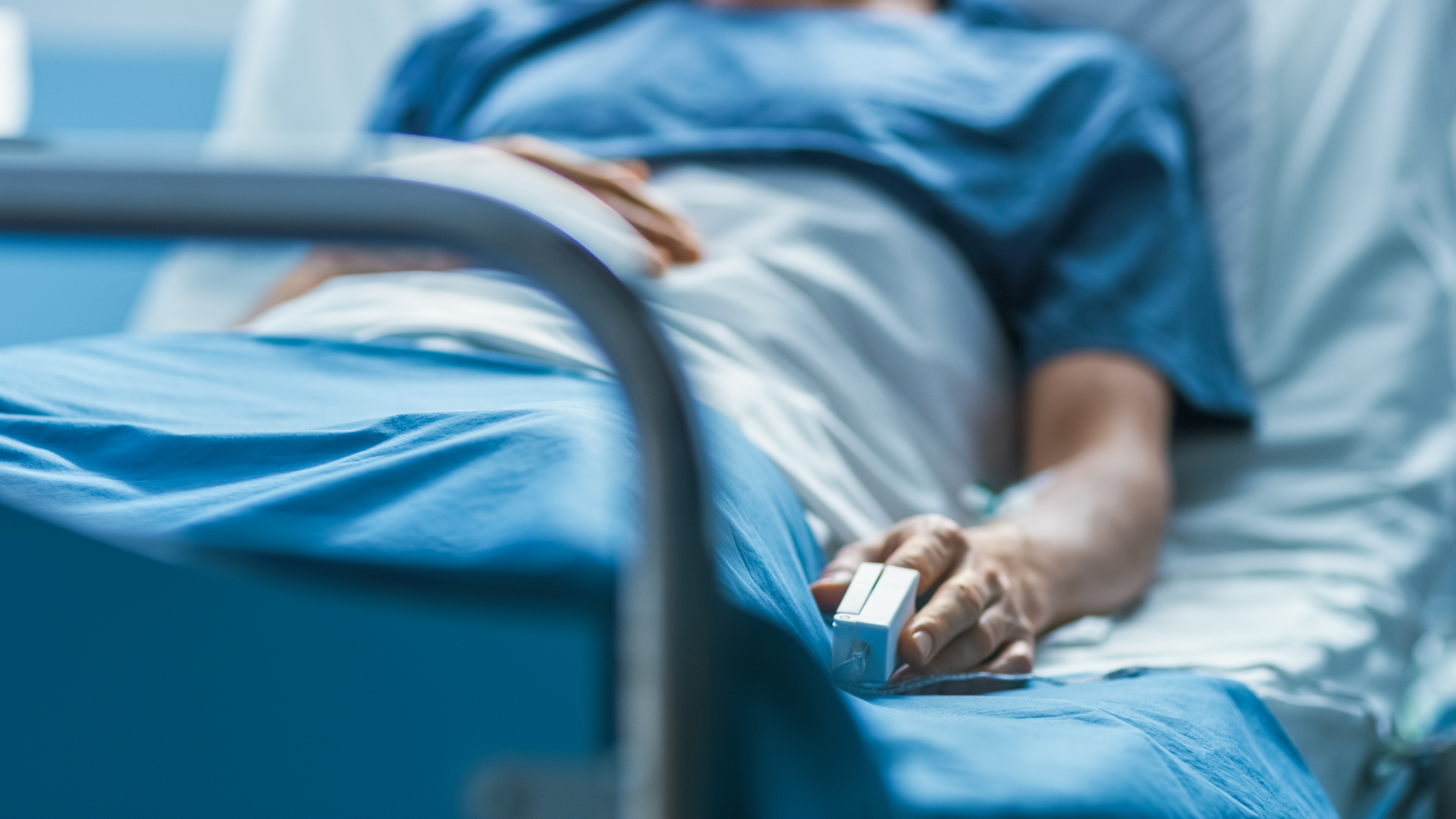 sick patient in hospital bed with heart rate monitor