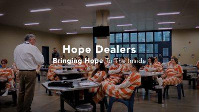 man teaching room full of female inmates in orange and white stripes