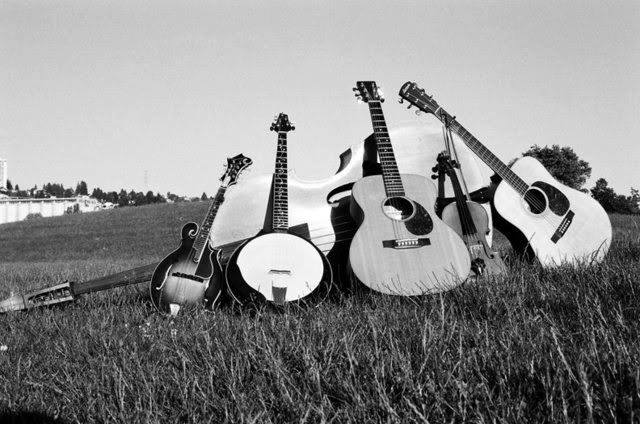 pile of guitars and banjos