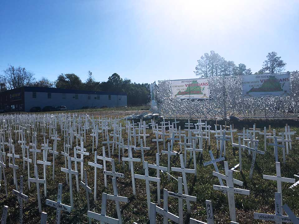 white crosses in ground sunny day building in the background