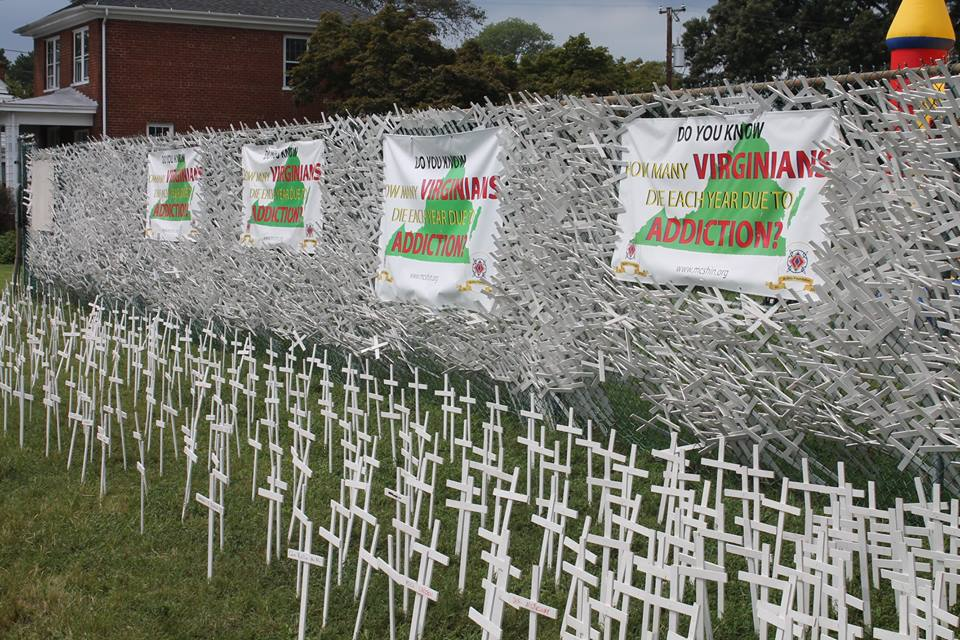 white crosses in ground with fence and banners